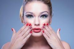 有手指的惊奇的年轻秀丽妇女在她的面孔 免版税库存图片