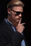 有手指的有胡子的商人在嘴 库存图片