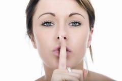 有手指的秘密的少妇在嘴唇 免版税图库摄影
