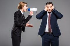 有手提式扬声机的恼怒的女实业家尖叫对商人 库存照片