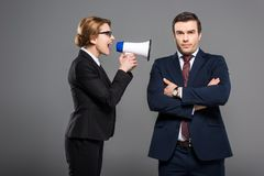 有手提式扬声机的积极的女实业家叫喊对商人, 库存图片