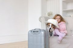 有手提箱和一条狗的一个小女孩在内部 免版税库存照片