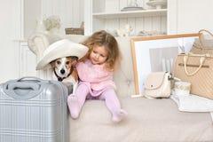 有手提箱和一条狗的一个小女孩在内部 库存照片
