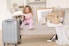 有手提箱和一条狗的一个小女孩在内部 免版税库存图片