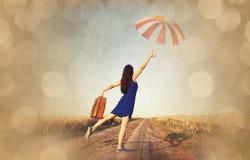 有手提箱和伞的女孩 免版税库存照片