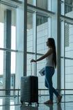 有手提箱和文件的女孩旅客为下次旅行做准备 女孩在机场站立 trav的概念 免版税库存图片