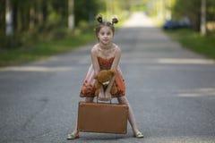 有手提箱和玩具熊的小女孩是在路 免版税库存图片