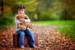 有手提箱和玩具熊的小男孩 免版税库存照片