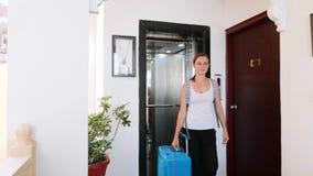 有手提箱和背包的年轻女人出去推力离开旅馆 股票录像