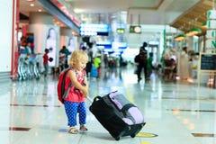 有手提箱旅行的小女孩在机场 免版税图库摄影