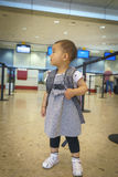 有手提箱旅行的小女孩在机场 免版税库存图片