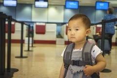 有手提箱旅行的小女孩在机场 免版税库存照片