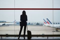 有手提行李的妇女在国际机场,注视着通过窗口飞机 库存照片