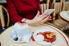 有手机、咖啡和蛋糕的手 库存图片