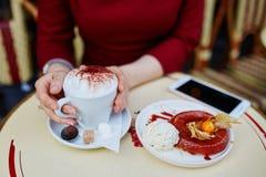 有手机、咖啡和蛋糕的手 图库摄影