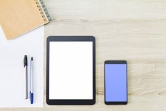 有手机、笔记本、纸和笔的空白的白色屏幕片剂计算机在木书桌上 库存照片