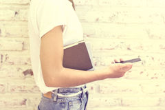 有手机和书的行家女孩 免版税图库摄影