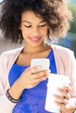 有手机和咖啡的蓬松卷发妇女 免版税库存照片