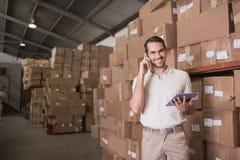 有手机和数字式片剂的工作者在仓库里 免版税库存图片