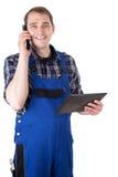 有手机和数字式片剂的微笑的工匠 免版税库存照片