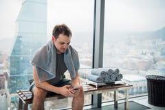有手机和毛巾的英俊的人有断裂在锻炼以后在健身房 免版税库存照片