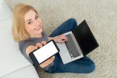有手机和膝上型计算机的妇女坐地毯 免版税库存照片