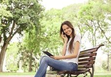 有手机和e书的女孩在公园 免版税库存图片