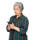 有手机的亚裔资深女性 免版税库存图片