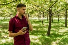 有手机的人在夏天公园 有sm的年轻英俊的人 免版税库存图片
