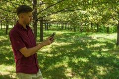 有手机的人在夏天公园 有sm的年轻英俊的人 免版税库存照片