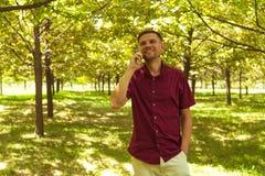 有手机的人在夏天公园 有sm的年轻英俊的人 免版税图库摄影