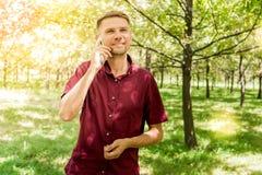 有手机的人在夏天公园 有sm的年轻英俊的人 库存图片