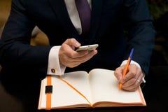 有手机的人在运作的桌上坐他的笔记本 免版税库存照片