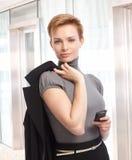 有手机的可爱的典雅的女实业家 库存图片