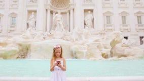 有手机的可爱的小女孩户外温暖的天在著名Fontana di Trevi附近的欧洲城市 股票视频