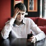 有手机的哀伤的少年 库存图片