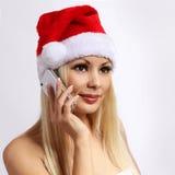 有手机的圣诞老人女孩。白肤金发的愉快的少妇 免版税库存照片