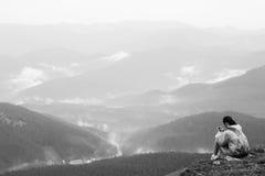 有手机的女孩在山顶部 免版税库存照片