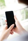 有手机的妇女在接触在一空白的scre的手上 免版税库存照片