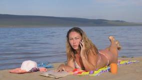 有手机的妇女在海滩 股票录像