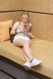 有手机的少妇在客厅 免版税库存照片