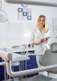 有手机的少妇牙医在牙齿办公室 免版税图库摄影