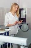 有手机的少妇牙医在牙齿办公室 免版税库存照片