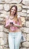 有手机的微笑的美丽的女孩 免版税库存照片