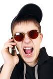 有手机的恼怒的少年 免版税图库摄影