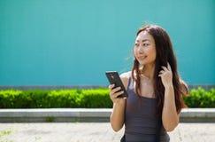 有手机的愉快的微笑的亚裔女孩读消息,蓝色背景 免版税图库摄影