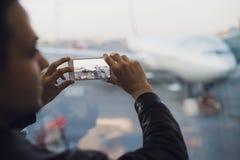有手机的旅客在拍他的航空器的照片机场 在的航空交通管制设施 图库摄影
