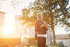 有手机的时髦的行家女孩在站立户外在大学附近的手上 库存图片
