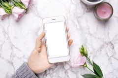 有手机的木手在与桃红色花的大理石办公室背景 库存图片
