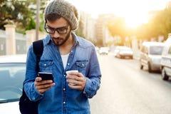 有手机的现代年轻人在街道 库存照片